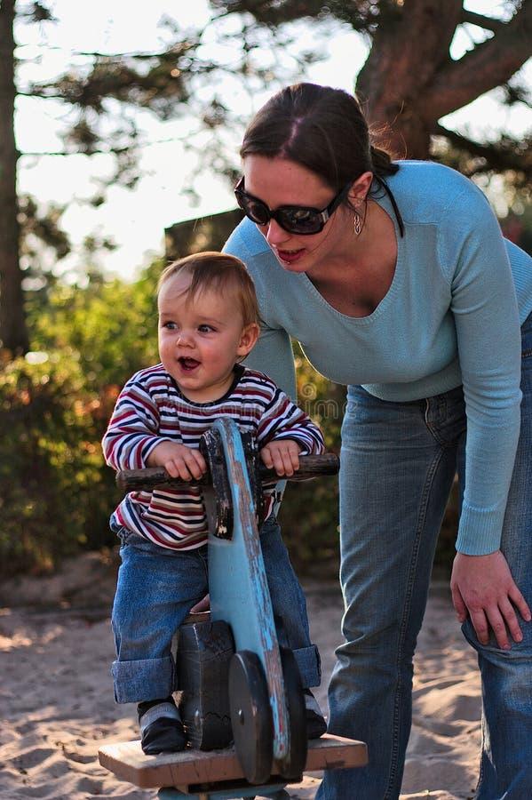Ragazzo con la madre sul campo da giuoco fotografia stock