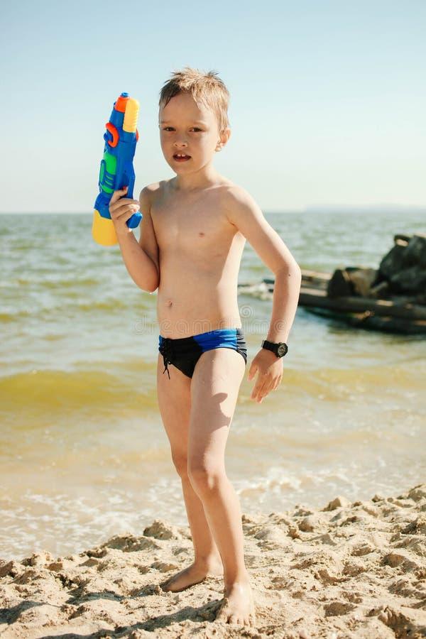 Ragazzo con la pistola a acqua e l'orologio impermeabile fotografia stock libera da diritti