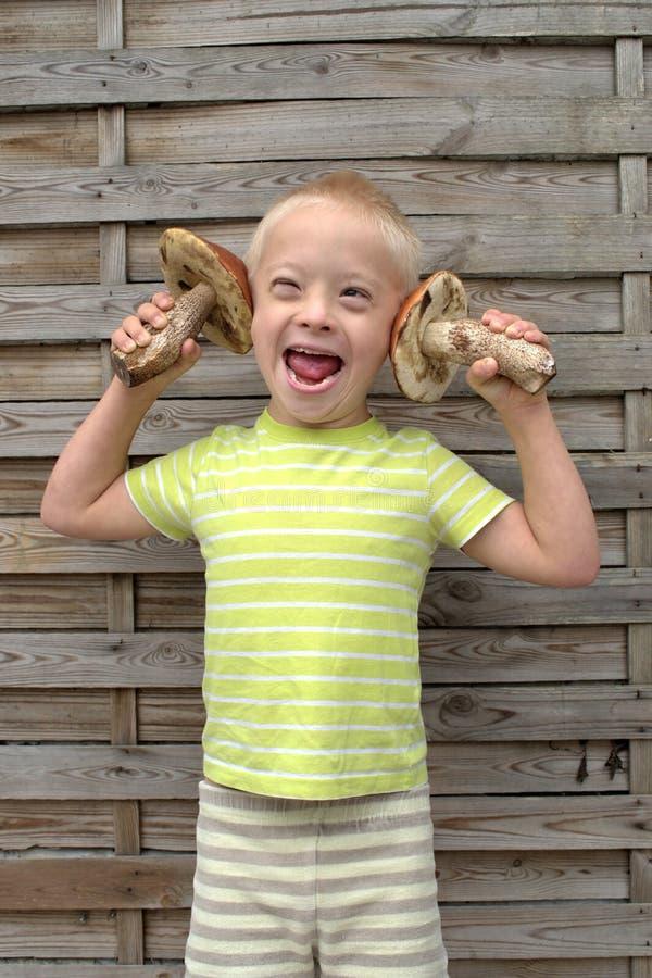 Ragazzo con la sindrome che tiene due funghi arancio fotografia stock