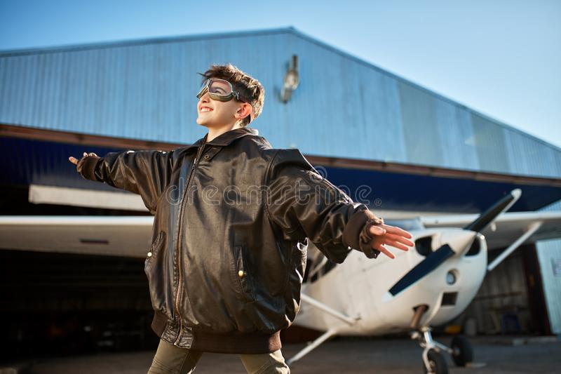 Ragazzo con le mani a parte come le ali, stanti fuori del capannone, in grande rivestimento pilota immagini stock