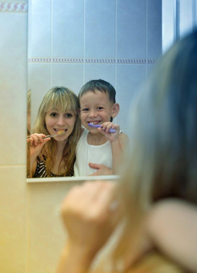 Ragazzo con sua madre per pulire i loro denti davanti allo specchio fotografie stock