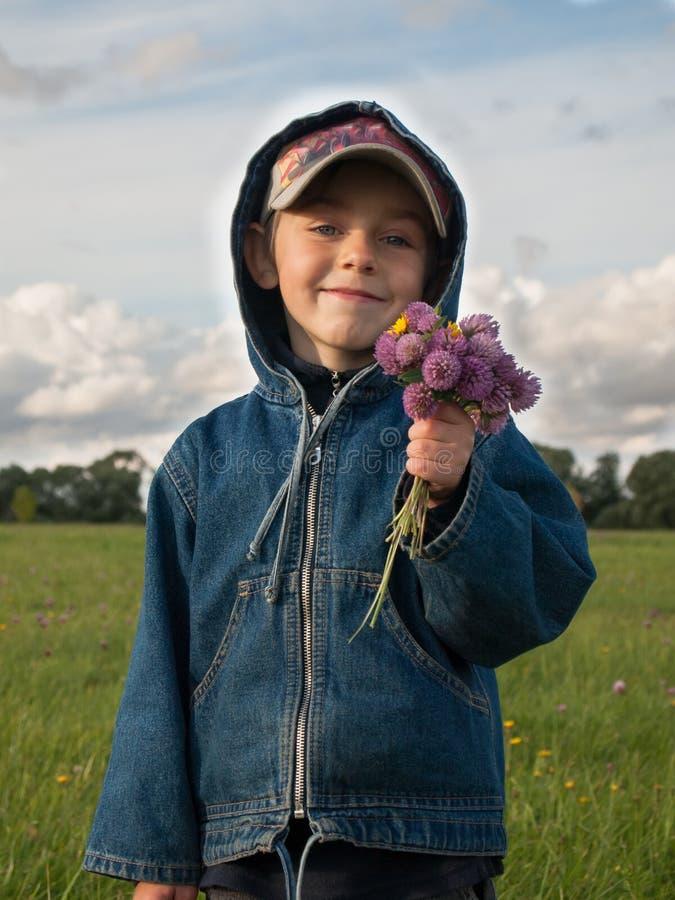 Ragazzo con un mazzo dei supporti di fiori in un campo fotografia stock