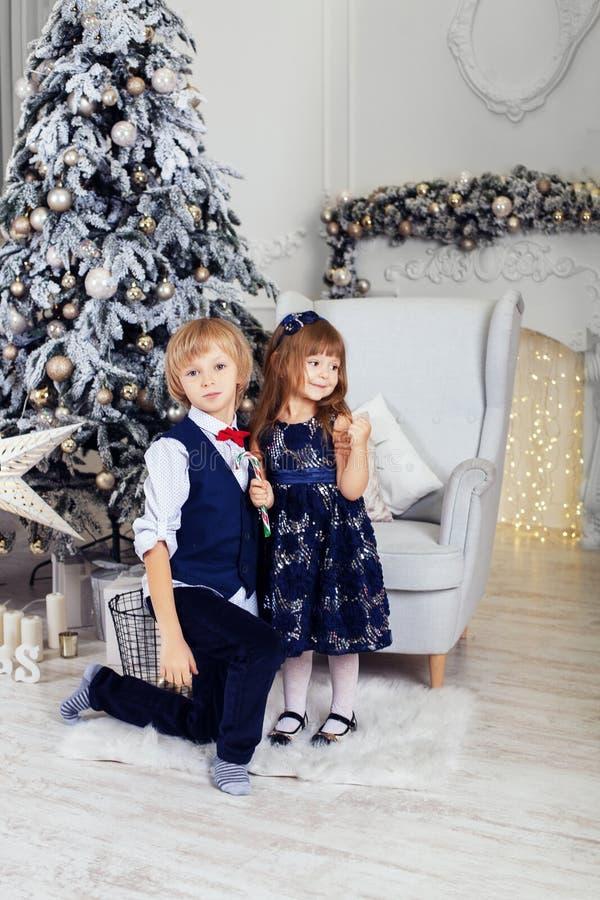 Ragazzo con una bambina che gioca vicino all'albero di Natale Il concentrato fotografia stock libera da diritti