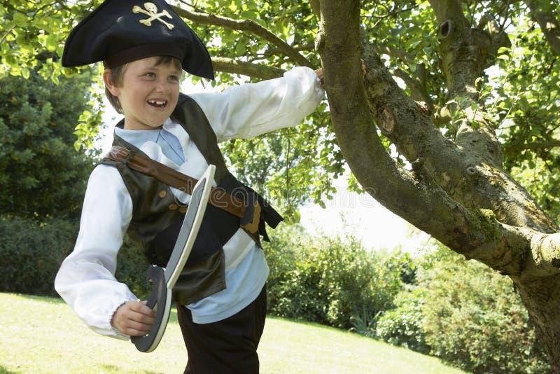 Ragazzo in costume del pirata che oscilla dall'albero fotografia stock libera da diritti