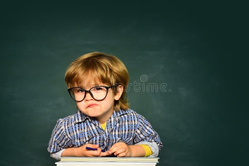 Ragazzo da scuola elementare al cortile della scuola Piccolo ragazzo prescolare sveglio del bambino in un'aula fotografie stock
