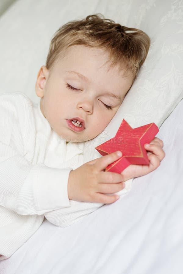 Ragazzo del bambino che dorme dolce con un giocattolo immagine stock