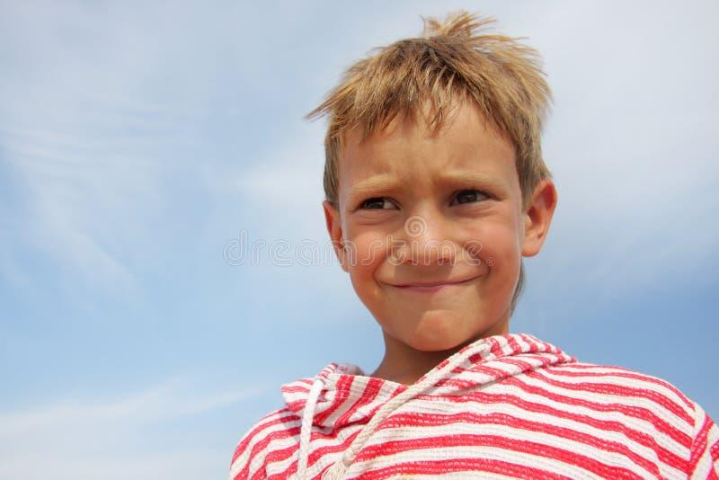 Ragazzo del bambino che fa i fronti sopra la priorità bassa del cielo fotografia stock