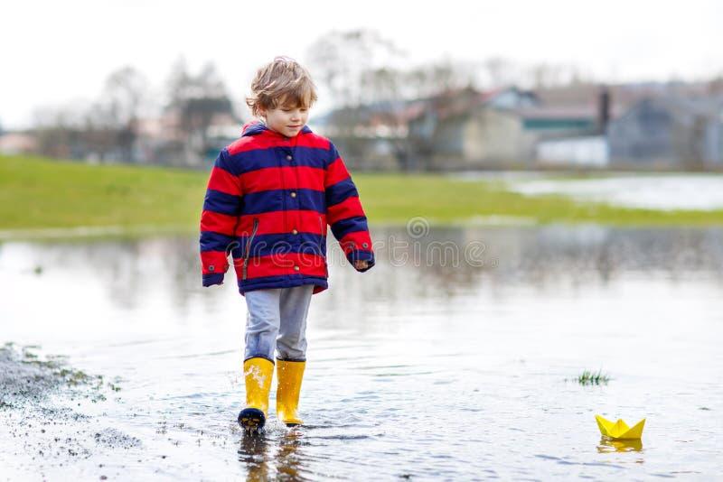 Ragazzo del bambino che gioca con la barca di carta dalla pozza fotografia stock libera da diritti