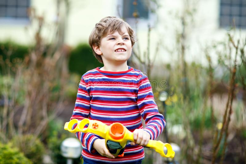 Ragazzo del bambino che gioca con la pistola a acqua nel giardino di primavera Divertiresi ed azione di scolaro fotografie stock libere da diritti