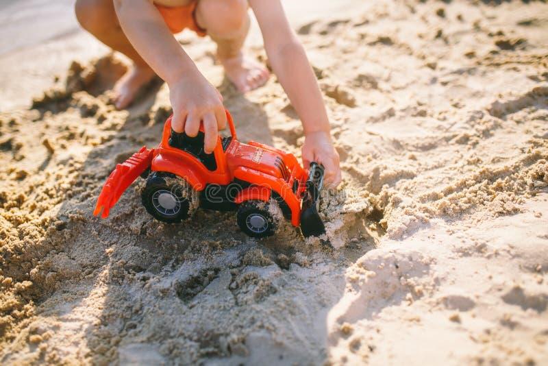 Ragazzo del bambino che gioca sulla spiaggia vicino al trattore di rosso del giocattolo del fiume immagini stock