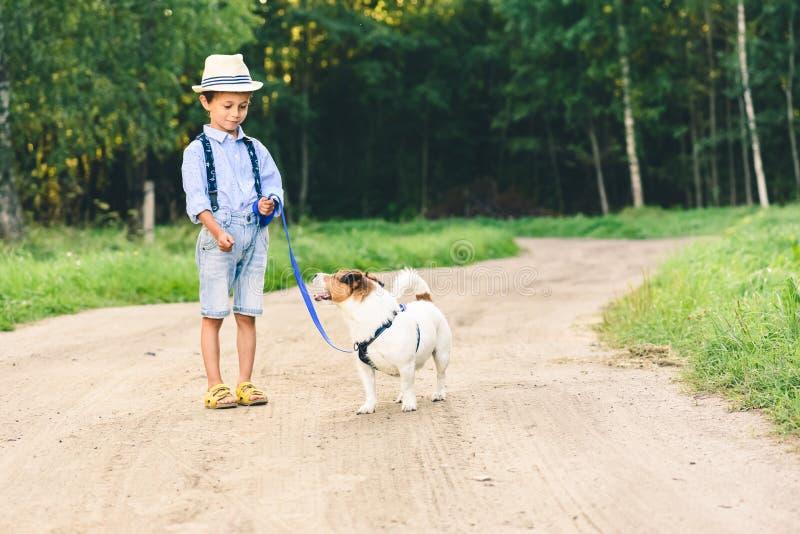 Ragazzo del bambino che impara come domare e preparare una passeggiata del cane sul guinzaglio immagine stock libera da diritti