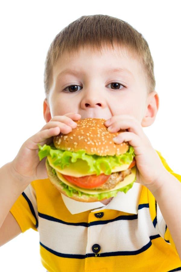 Ragazzo del bambino che mangia hamburger delizioso isolato fotografie stock