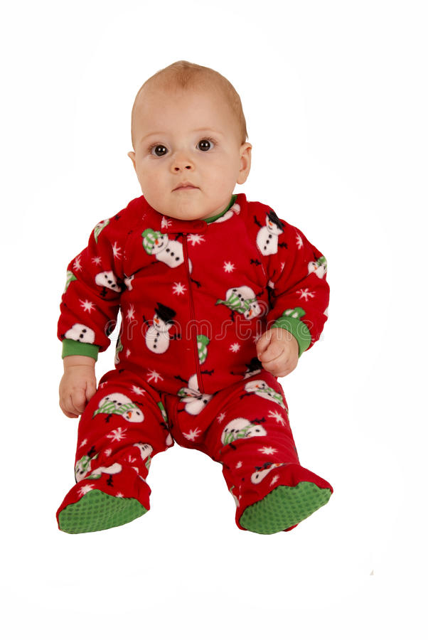 Ragazzo del bambino che si siede in pigiami rossi del pupazzo di neve fotografia stock