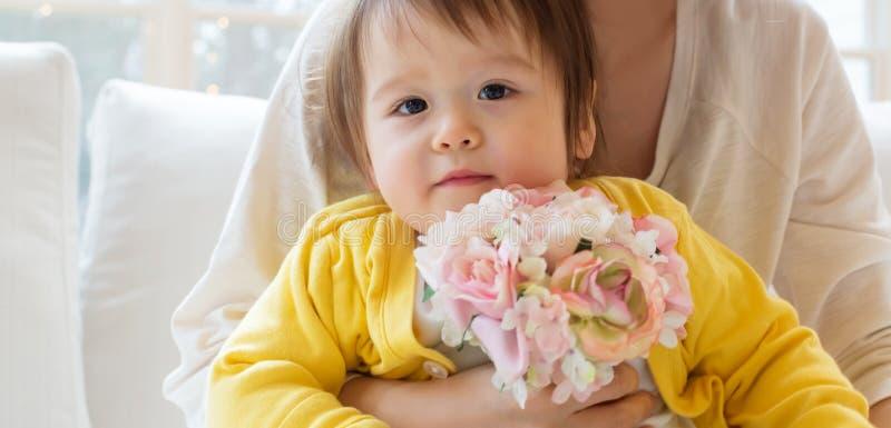 Ragazzo del bambino con i suoi fiori della tenuta della madre immagini stock