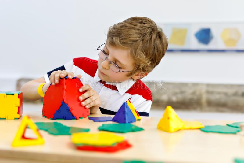 Ragazzo del bambino con i vetri che giocano con il corredo di plastica lolorful degli elementi in scuola o nella scuola materna d immagine stock
