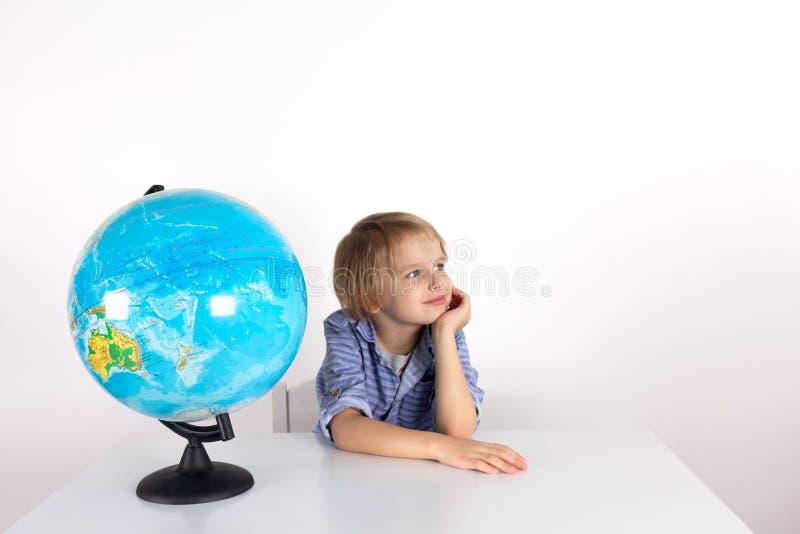 Ragazzo del bambino con un globo sulla lezione di vita pratica su un fondo bianco, classe di Montessori, isolato immagini stock