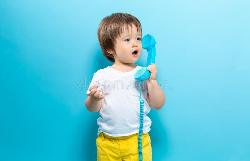Ragazzo del bambino con un telefono antiquato immagine stock libera da diritti