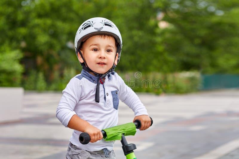 Ragazzo del bambino nella guida bianca del casco sulla sua prima bici con un casco bici senza pedali immagini stock