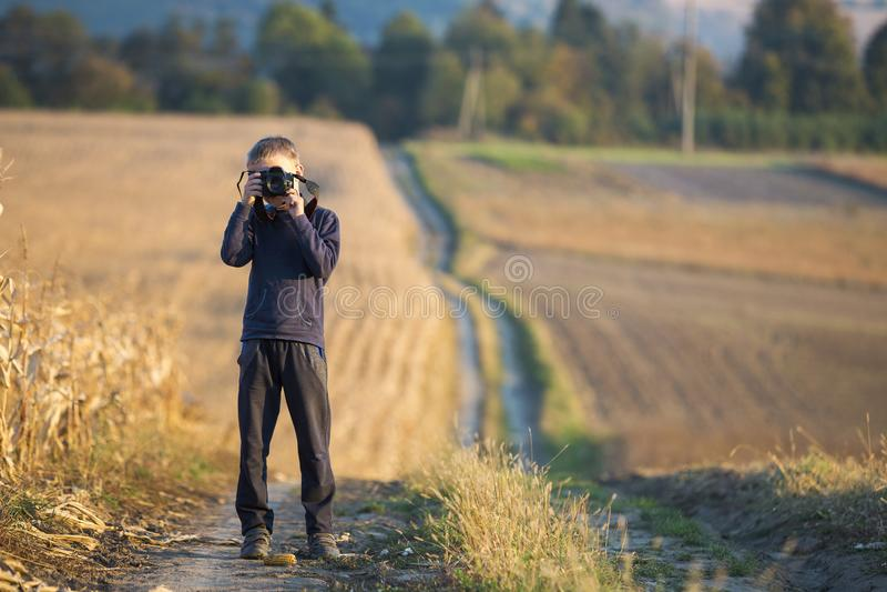 Ragazzo del bambino piccolo con la macchina fotografica della foto che prende immagine del giacimento di grano su fondo rurale va fotografia stock libera da diritti