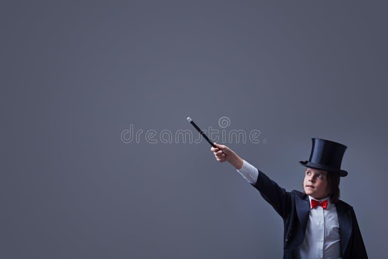Ragazzo del mago con l'elmetto protettivo che indica lo spazio della copia con la bacchetta magica fotografia stock