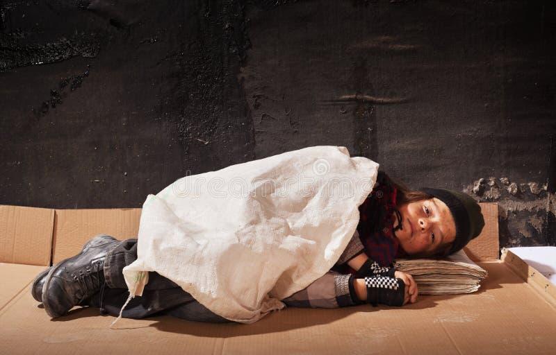 Ragazzo del mendicante che dorme sullo strato del cartone immagine stock libera da diritti