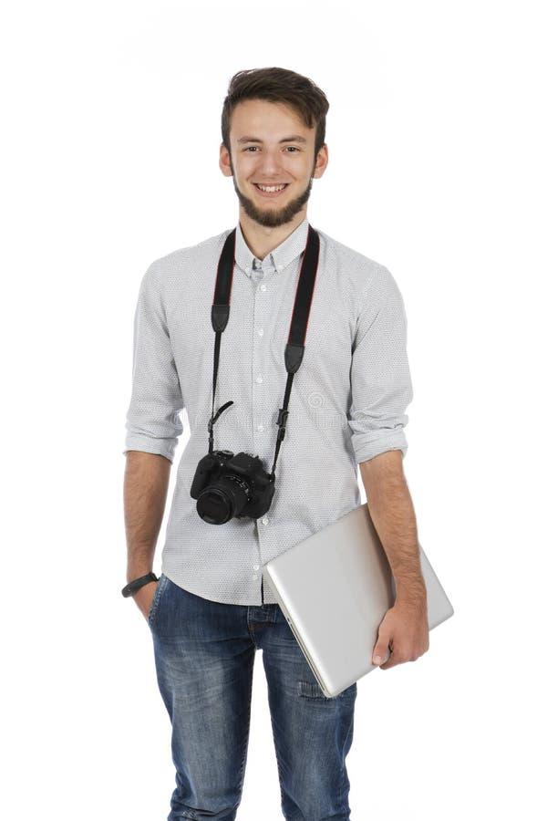 Ragazzo del nerd con la macchina fotografica intorno al suo collo e computer sotto il suo braccio immagine stock