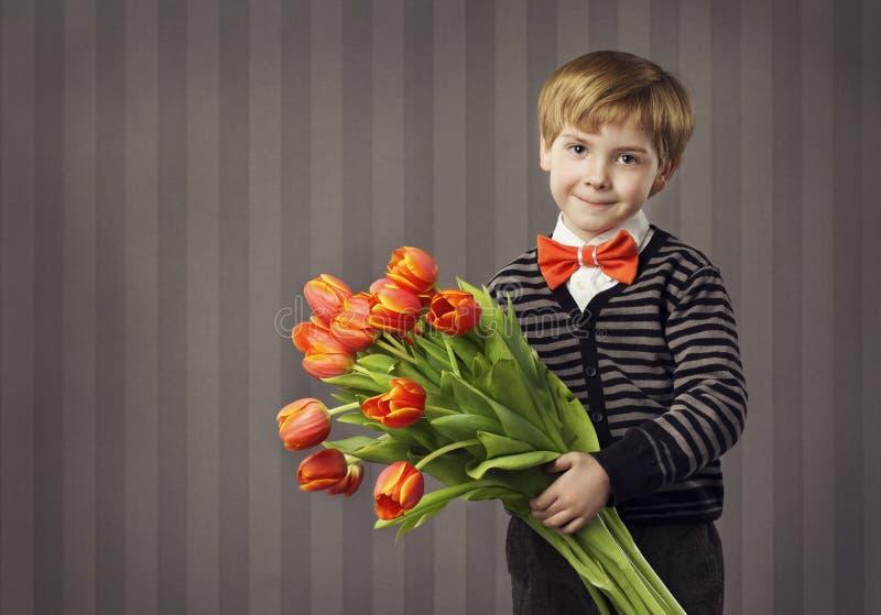 Ragazzo del piccolo bambino che dà il mazzo dei fiori, bambino bello R accogliente immagini stock