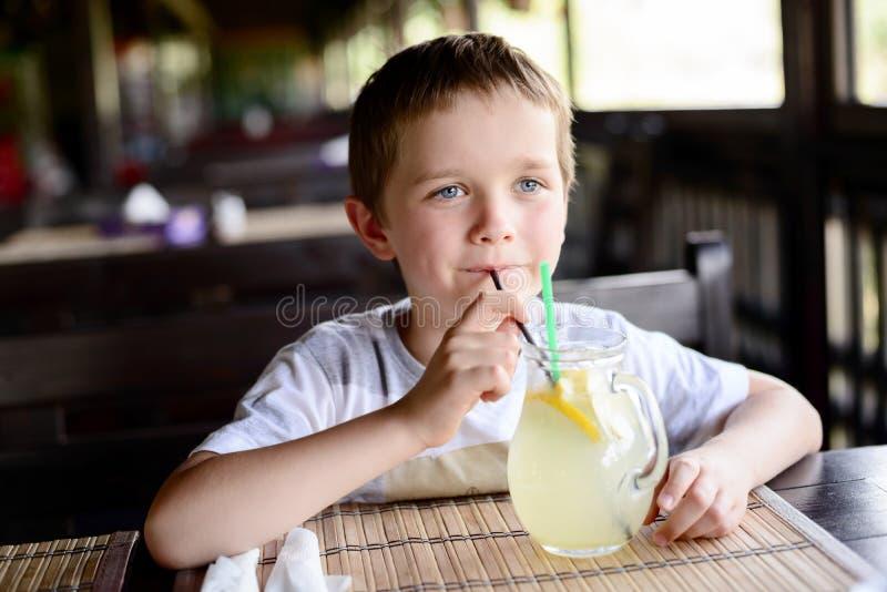 Ragazzo del piccolo bambino che gode della sua limonata deliziosa fotografia stock libera da diritti