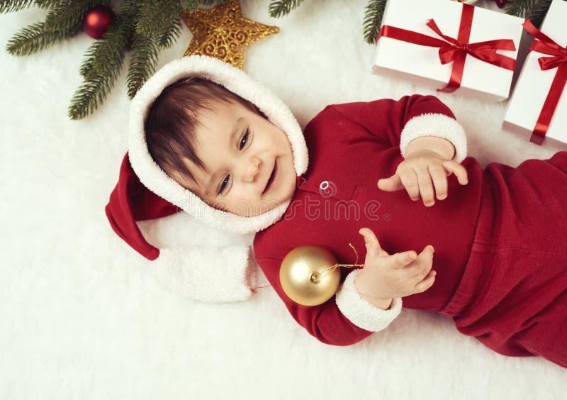 Ragazzo del piccolo bambino vestito come Santa che gioca con la decorazione di natale, bugia su pelliccia bianca, concetto di vac immagini stock