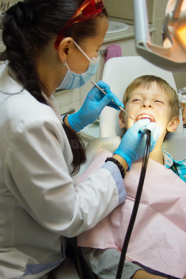 Ragazzo del primo piano che apre il suo bocca largamente durante l'ispezione della cavità orale dal dentista immagini stock libere da diritti