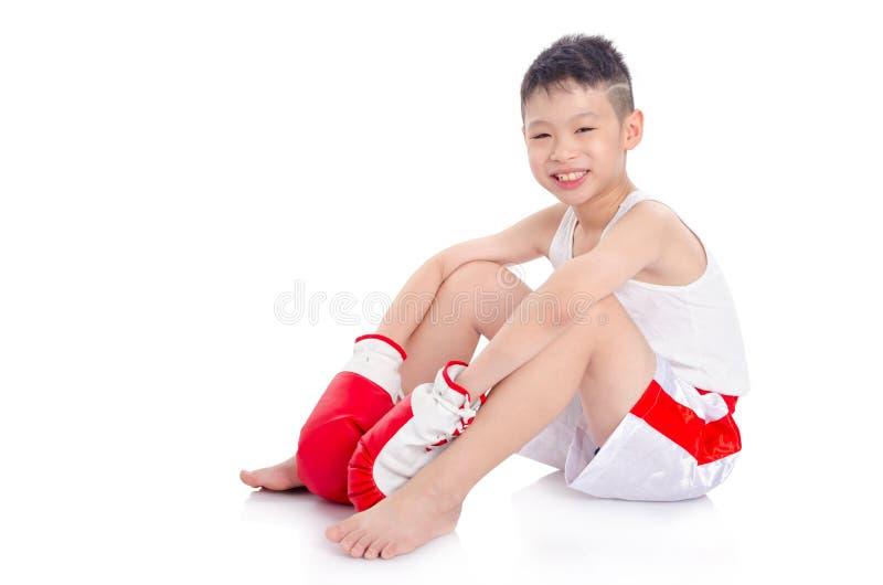 Ragazzo del pugile che si siede sul pavimento sopra fondo bianco fotografia stock