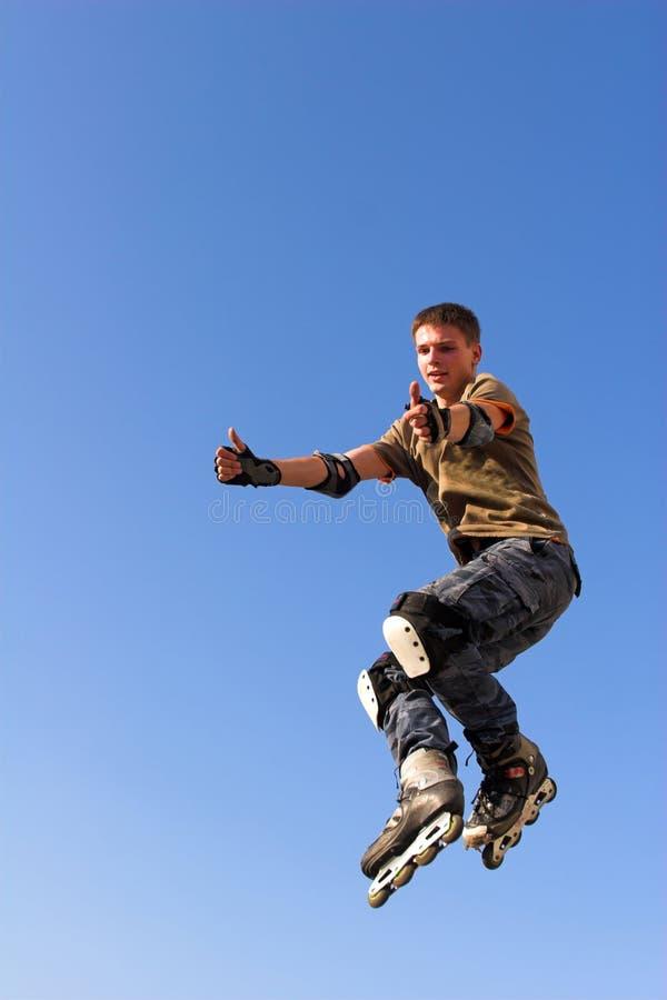 Ragazzo del rullo che salta dal parapetto sul cielo blu fotografie stock