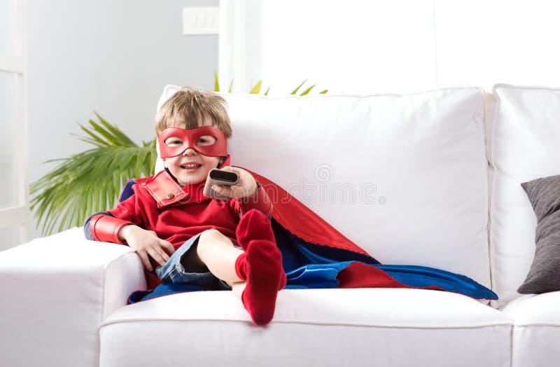 Ragazzo del supereroe che guarda TV immagine stock
