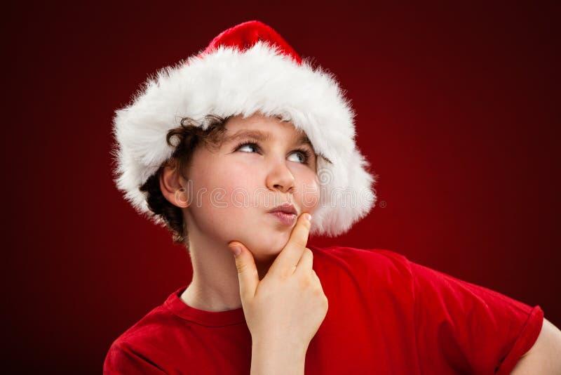Ragazzo del tempo di Natale con Santa Claus Hat fotografia stock libera da diritti