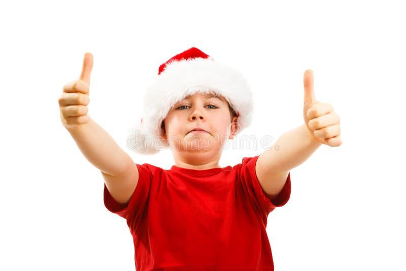 Ragazzo del tempo di Natale con Santa Claus Hat che mostra segno giusto fotografia stock