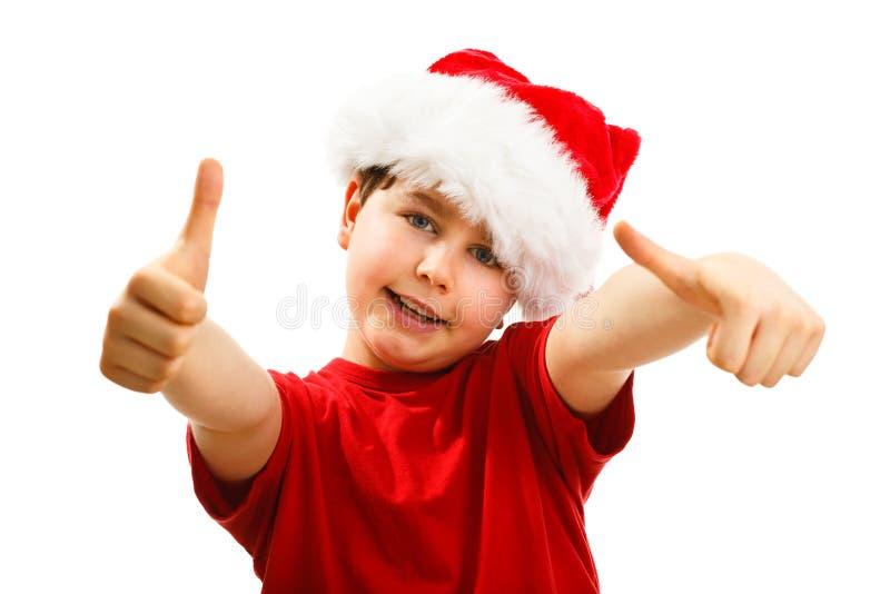 Ragazzo del tempo di Natale con Santa Claus Hat che mostra segno giusto fotografie stock