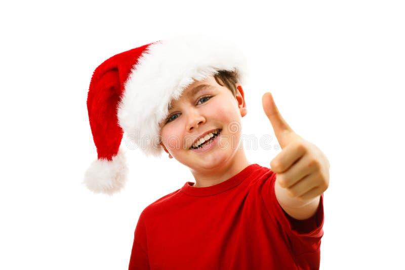 Ragazzo del tempo di Natale con Santa Claus Hat che mostra segno giusto immagine stock libera da diritti