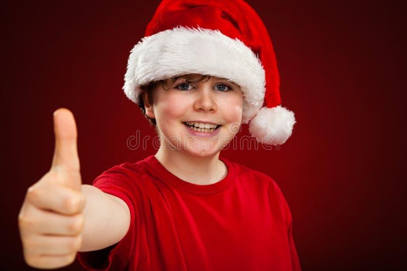 Ragazzo del tempo di Natale con Santa Claus Hat che mostra segno giusto immagini stock