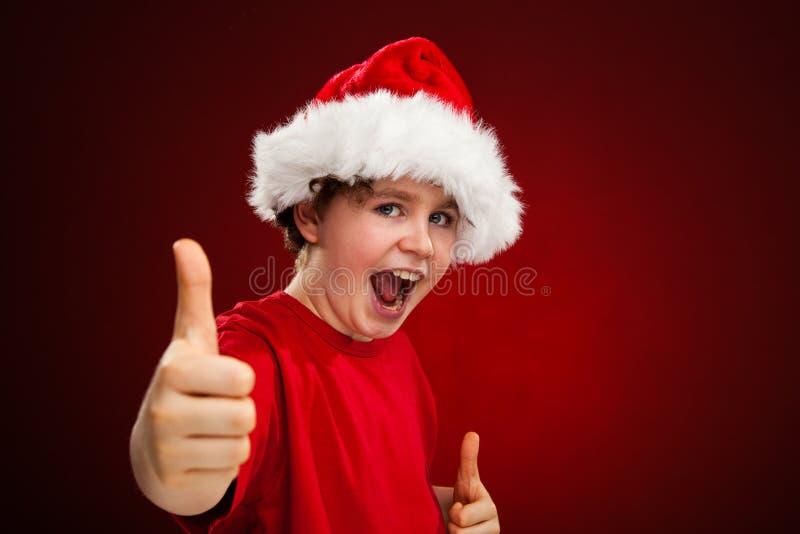 Ragazzo del tempo di Natale con Santa Claus Hat che mostra segno giusto fotografia stock libera da diritti