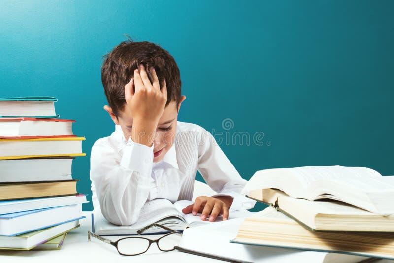 Ragazzo del ute del ¡ di Ð che legge libro difficile alla tavola, fondo blu fotografia stock