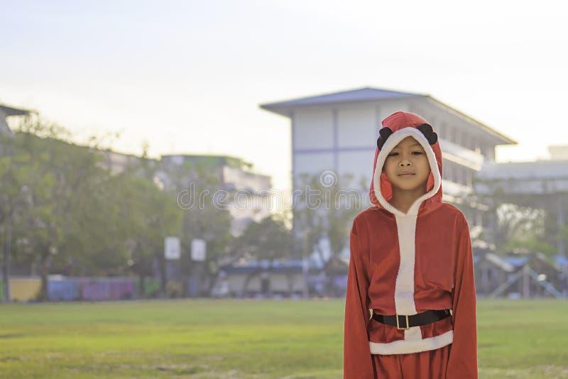 Ragazzo dell'Asia che indossa un fondo rosso di Natale sul prato inglese della scuola fotografia stock libera da diritti