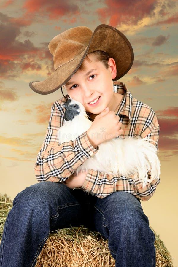 Ragazzo dell'azienda agricola che si siede sulla balla di fieno che tiene un pollo immagini stock libere da diritti
