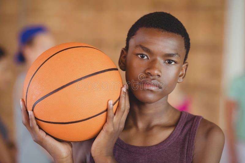 Ragazzo della High School che sta con la pallacanestro nella corte immagini stock