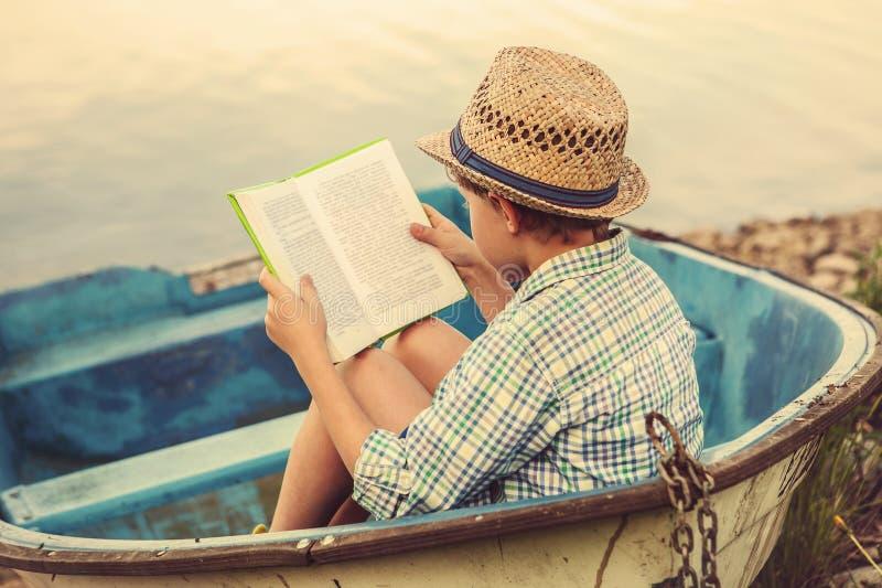 Ragazzo della lettura in vecchia barca fotografia stock