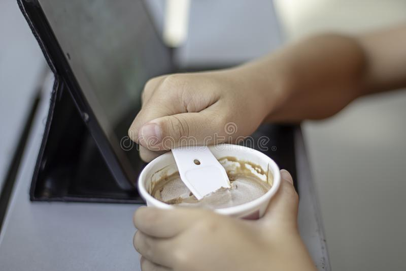 Ragazzo della mano che tiene il ripartitore del cucchiaio in una tazza fotografia stock libera da diritti