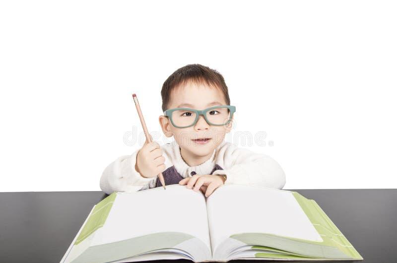 Ragazzo dello scolaro in libro di studio di vetro fotografia stock libera da diritti