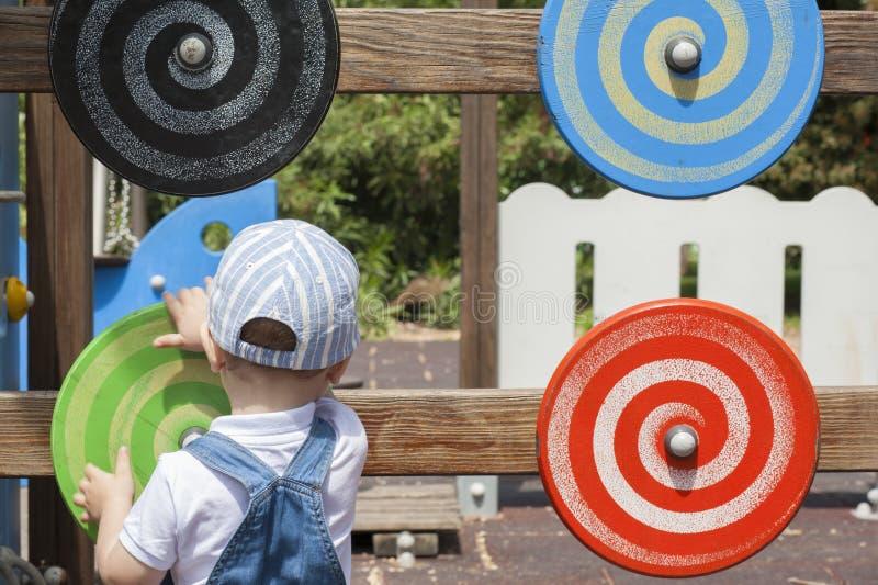 Ragazzo di 2 anni che gioca con il disco a spirale di legno al campo da giuoco fotografia stock