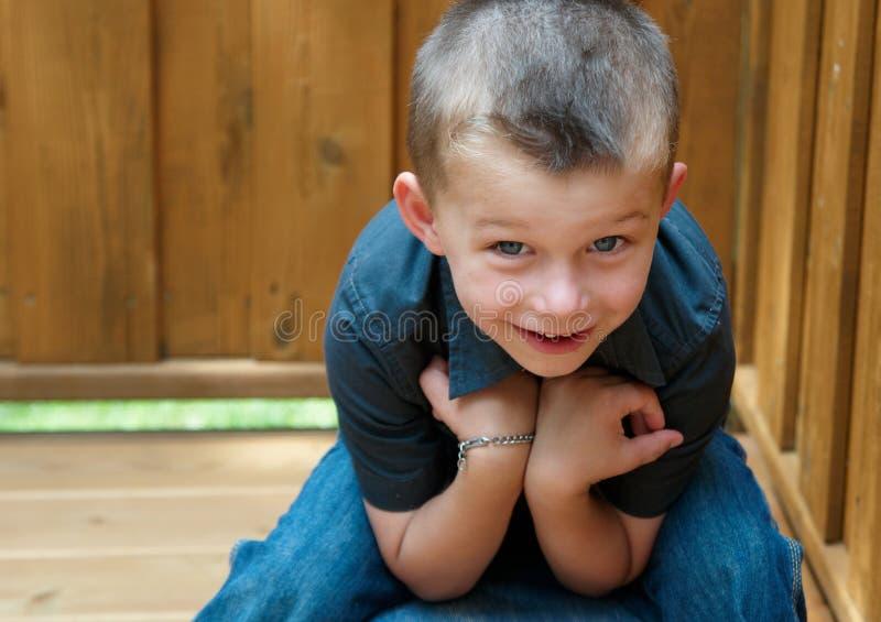Ragazzo di 5 anni che si siede sulla piattaforma immagini stock