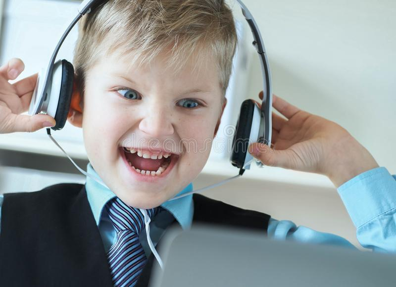 Ragazzo di 6 anni sveglio in vestito che ascolta la musica o l'audio esercitazione sulle cuffie ai precedenti dell'ufficio fotografie stock libere da diritti