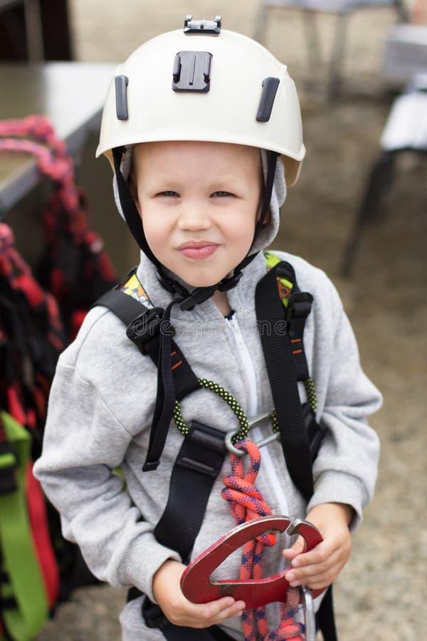 Ragazzo di 5 anni in un casco ed attrezzatura per alpinismo immagini stock libere da diritti